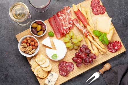 Cheese, meat, grapes and olives antipasto. Appetizer selection plate and glasses with red and white wine. Top view. Flat lay 免版税图像
