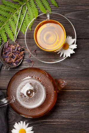 Herbal tea in teapot and cup on wooden table. Top view. Flat lay