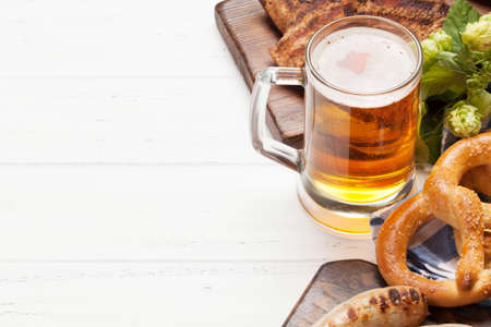 Oktoberfest set. Pretzels, sausages, meat and lager beer mug on wooden background. With copy space