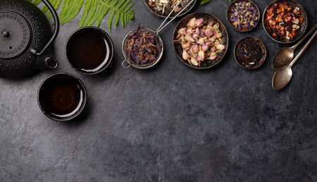 Various herbal dry tea, teapot and cup on stone table. Top view with copy space. Flat lay 免版税图像
