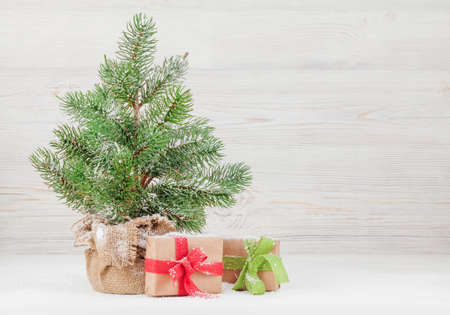 Christmas greeting card with small fir tree and gift boxes in front of wooden wall and copy space for your xmas greetings
