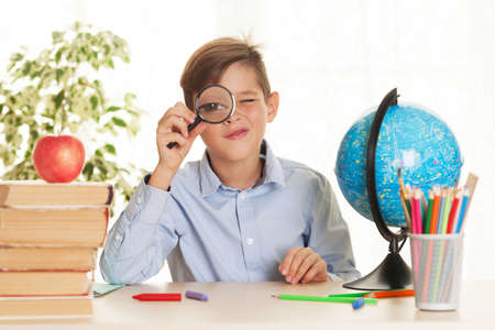 Young schoolboy sitting at the table and doing homework. Elementary education concept