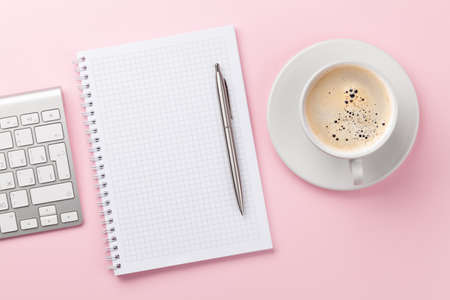 Pink workplace desk table with computer, notepad and coffee. Top view with space for your text. Flat lay