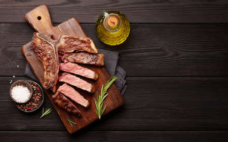 T-bone grilled beef steak with spices and herbs. Top view flat lay with copy space