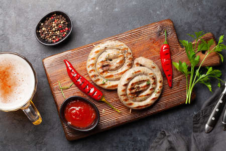 Grilled sausages with spices and herbs and glass of beer. Top view flat lay