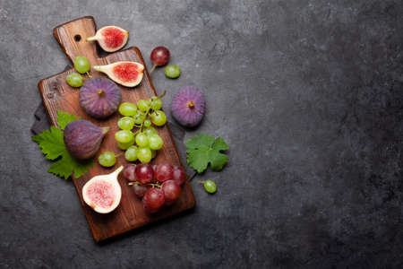 Ripe sweet figs and grapes. Top view flat lay with copy space 免版税图像