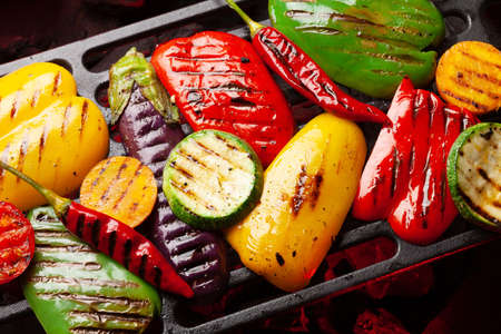 Grilled vegetables cooking on coal grill with spices and herbs