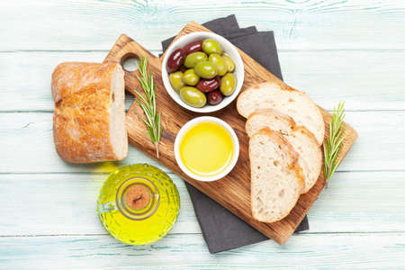 Ripe olives, olive oil and ciabatta bread. Top view flat lay 免版税图像