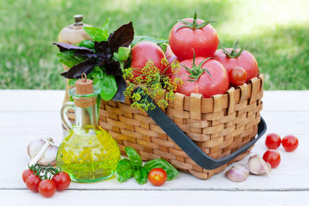 Italian cuisine ingredients. Ripe tomatoes, herbs and spices on garden table 免版税图像