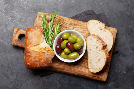 Ripe olives and ciabatta bread on cutting board. Top view flat lay