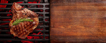 T-bone beef steak cooking on grill. Top view flat lay. With cutting board for copy space
