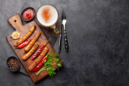 Grilled sausages with spices and herbs and glass of beer. Top view flat lay. With copy space 免版税图像