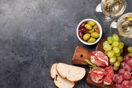 Antipasto plate with prosciutto, olives and grapes. Appetizer board and white wine. Top view flat lay with copy space