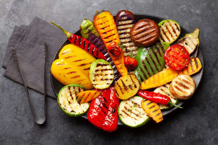 Grilled vegetables on plate with spices and herbs. Top view flat lay