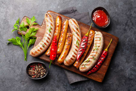 Grilled sausages with spices and herbs. Top view flat lay 免版税图像