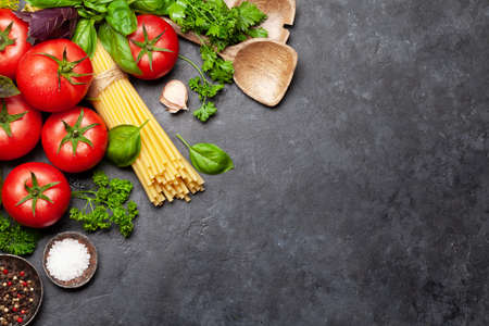 Italian cuisine ingredients. Garden tomatoes, pasta, herbs and spices. Top view with copy space. Flat lay