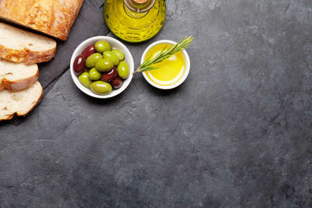 Ripe olives, olive oil and ciabatta bread. Top view flat lay with copy space
