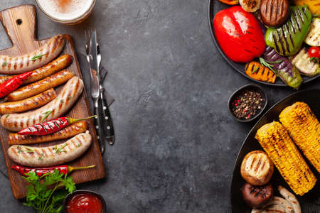 Grilled sausages and vegetables with spices and herbs. Top view flat lay with copy space 免版税图像