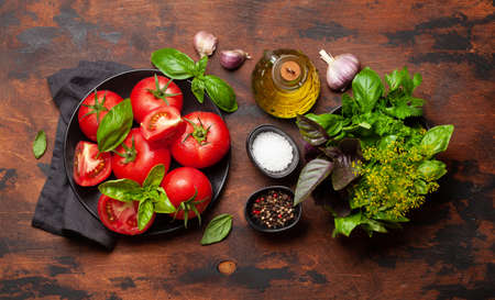 Italian cuisine ingredients. Garden tomatoes, herbs and spices. Top view. Flat lay