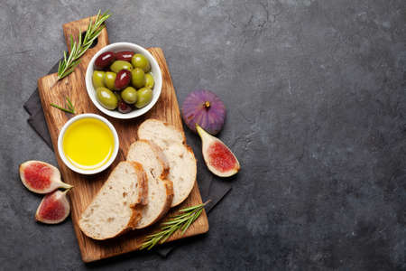 Ripe olives, olive oil, figs and ciabatta bread. Top view flat lay with copy space 免版税图像