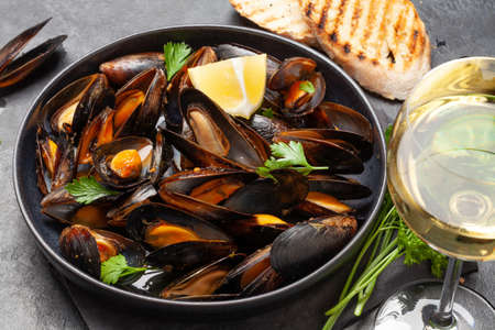 Traditional seafood mussels in wine sauce and baguette toasts Stock fotó