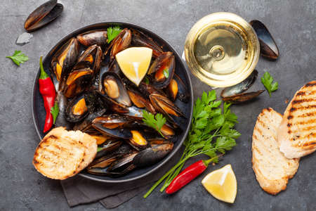 Traditional seafood mussels with baguette toasts and white wine. Top view flat lay Stock fotó