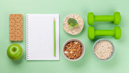 Healthy food and weigh loss concept. Top view flat lay with notepad for your fitness or diet plan