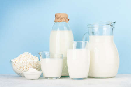 Various dairy products. Milk, cheese, cottage, sour cream. In front of blue background Stock fotó