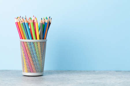 Colorful pencils. Office supplies or school items in front of blue wall with copy space for your text Stockfoto