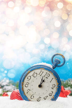 Christmas greeting card with alarm clock and decor in snow over blurred bokeh background and copy space for your xmas greetings
