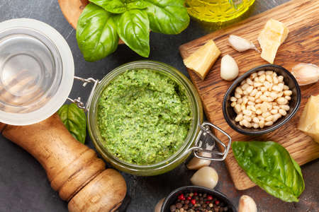 Homemade pesto sauce with basil leaves, pine nuts, parmesan and garlic. Top view flat lay