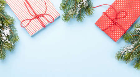 Christmas gift boxes and fir tree over blue background with space for your greetings. Top view flat lay