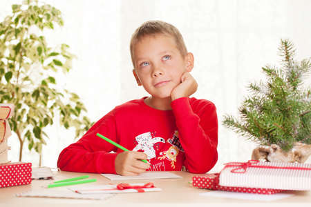 Little boy writes a letter to Santa Claus about christmas gift and wishes