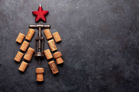 Christmas greeting card with fir tree shaped corkscrew and corks. Top view flat lay with space for your xmas greetings or holiday recipe