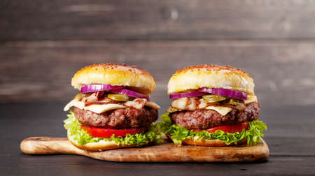 Homemade tasty burgers with big beef, cheese, tomato, bacon and lettuce. With copy space