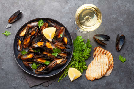 Traditional seafood mussels with baguette toasts and white wine. Top view flat lay