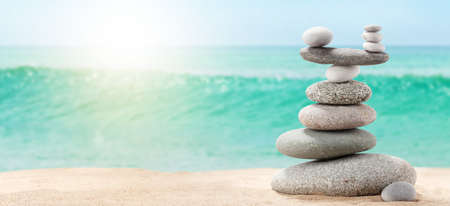 Pyramid of sea pebbles on a sunny sand beach. Life balance and harmony concept