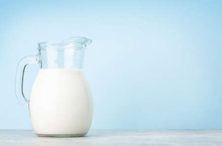 Milk in glass jug in front of blue background with copy space