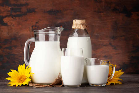 Milk in bottle, jug and glass. In front of wooden background