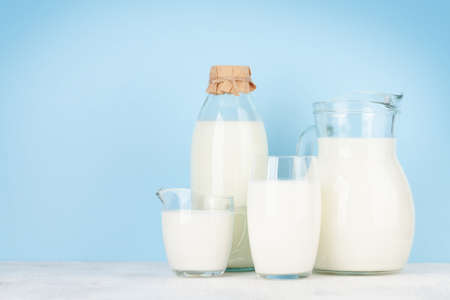Milk in bottle, jug and glass. In front of blue background. With copy space