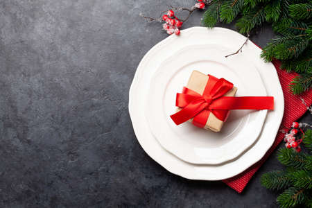 Christmas table setting with plate, gift box and xmas decor. Top view flat lay with copy space