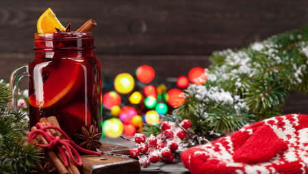 Christmas mulled wine with spices and citruses, xmas tree and lights bokeh