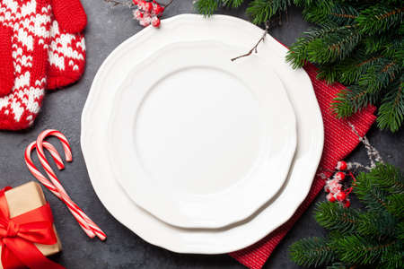 Christmas table setting with empty plate, gift box and xmas decor. Top view flat lay with copy space
