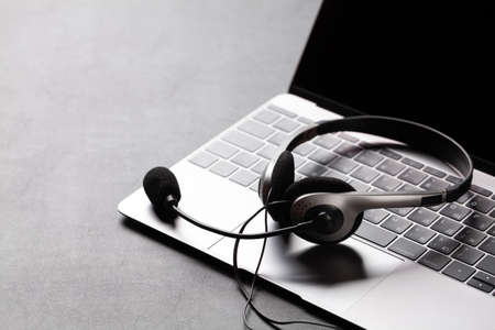 Office desk with headset and laptop. Remote office and work from home concept. With copy space