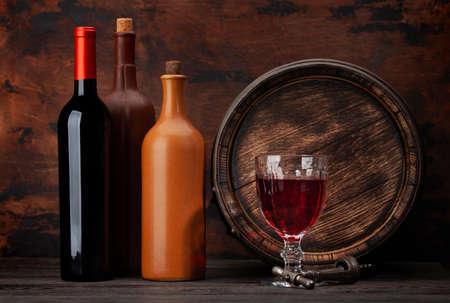 Wine bottles, glass, vintage corkscrew and old wooden barrel