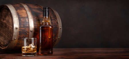 Scotch whiskey bottle, glass and old wooden barrel. With copy space