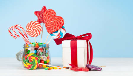 Various sweets assortment. Candy, bonbon, lollipop in glass can and gift box over blue background. With copy space