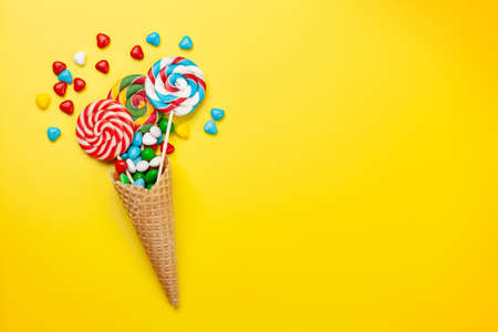 Various sweets assortment. Candy, bonbon and lollipop in ice cream cone on yellow background. Top view flat lay with copy space