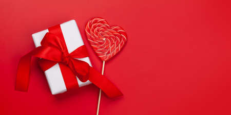 Valentines day greeting card template. Gift box and heart candy lollipop over red background. Top view flat lay with copy space Standard-Bild