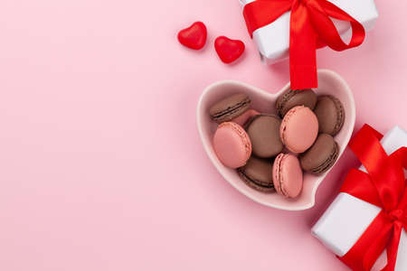 Valentines day with macaroons in heart shaped plate and gift boxes over pink background with copy space. Top view flat lay Standard-Bild